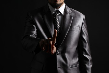 Business man pointing something by his finger in studio on black background