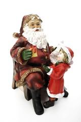 Santa Claus figurine handing small girl a Christmas present, Christmas decoration