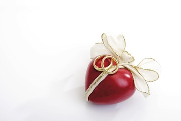 Bow wrapped around a red heart and wedding bands, symbol for marriage/engagement