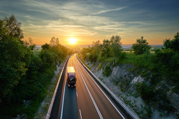 Fotobehang - Truck driving on the highway in a rural landscape at sunset. View from above.