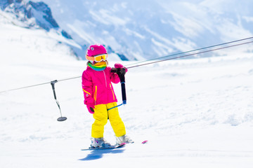 Child on ski lift in snow sport school in winter mountains