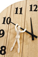 Wooden mannequin hanging from a clock, symbolic for stopping time