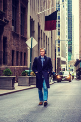 American man traveling in New York, wearing blue long overcoat, scarf, jeans, knit hat, carrying back bag, hands in pockets, walking on vintage street with high buildings. Car, biker on background..