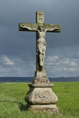 Jesus on the cross, stone statue in a field beneath storm clouds, Hassberge Mountains, Lower Franconia, Bavaria, Germany, Europe