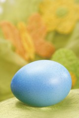 Pastel-coloured Easter egg in a nest with out-of-focus butterfly decoration in background