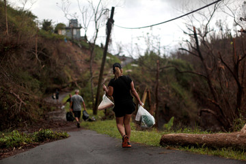 Local residents walk along a damaged road weeks after Hurricane Maria hit Puerto Rico in Barranquitas, Puerto Rico