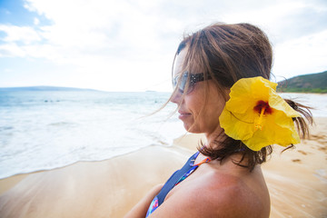 Pretty woman with hibiscus flower in her hair at a Hawaiian Beach
