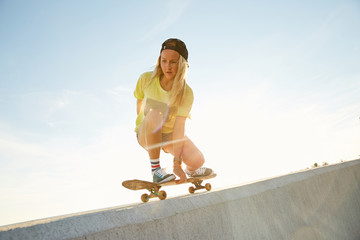 Girl skateboarding on a bank of the sea in the sunset in Sochi
