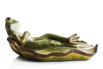 Frog figurine lying on a lily pad