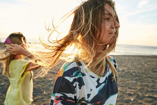 Girls having fun on the sea shore in sunset