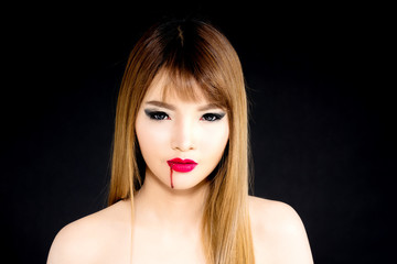 Young Asian woman vampire isolated on black background.