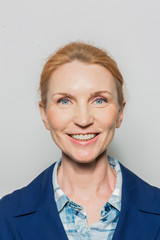Happy middle-aged woman with healthy smile looking at camera