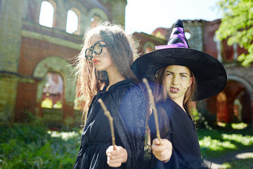 Cute witches in warlocks showing their magic wands and power