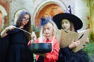 Little halloween witches with spell-book and magic stick preparing potion for tricks