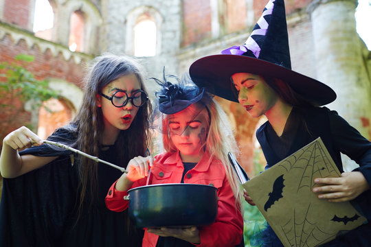 Gloomy halloween witches saying black magic spells over pot with poisonous brew