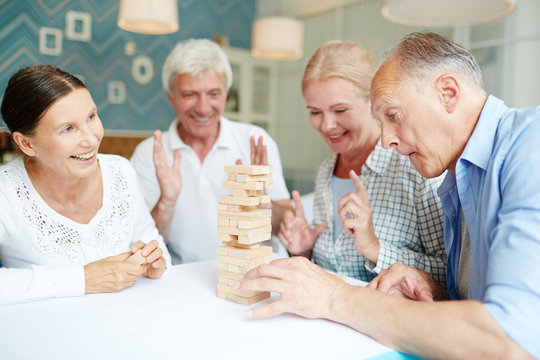 Enthusiastic senior friends playing broad game while spending peaceful evening at cozy living room with stylish design