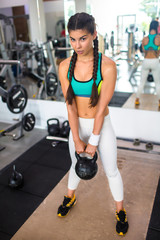 Full length portrait of pretty young sportswoman looking at camera while having training with kettlebell at gym