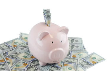 Pink piggy bank on US dollars isolated on white background