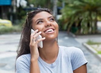 Beautiful latin female teenager at smart phone