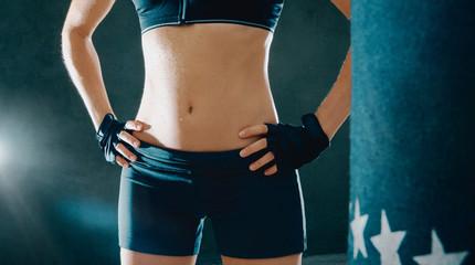 Donna sportiva fa boxe, addominali e muscoli