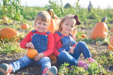 Happy girls sitting on big pumpkin at farm field patch
