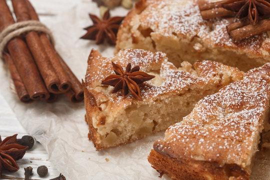 Homemade Apple pie with cinnamon, cardamom and star anise closeup. Traditional autumn cakes for tea. Selective focus