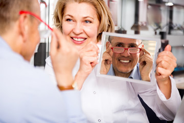 charming female consultant optician consulting mature male customer about frames
