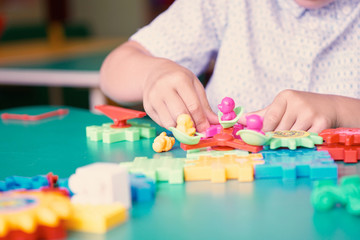 Little boy's hands playing with colorful plastic bricks at the table. Kids having fun and building out of bright constructor bricks. Early learning. Developing toys