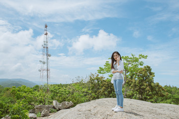 Asian woman talking on the phone at the top of a mountain stand on a rock look at camera.