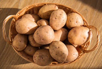 Fresh potatoes in a wicker basket on a wooden table.
