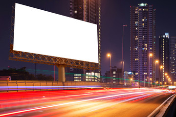 Blank billboard on light trails, street and urban in the night - can advertisement for display or montage product or business.