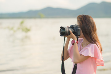 Beautiful Asian woman take picture at lake with a dslr. Copy space. Vacation or weekend concept.