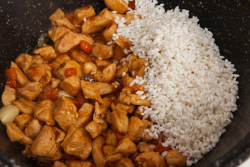 Chicken with vegetables and  rice in the frying pan