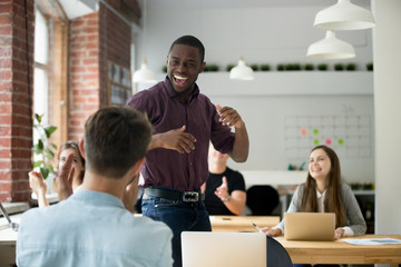 African american office worker dancing surrounded by colleagues. Happy entrepreneur performing victory dance, celebrating great achievement at work. Team of coworkers cheering him by clapping hands.