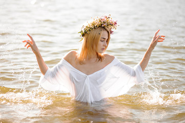 Girl in a white wet shirt and floral wreath standing in water