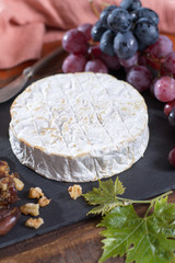 Famous French fresh soft cheese - camembert, delicious dessert with nuts and dried fruits