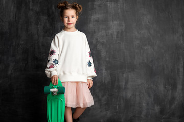 Fashionable little girl in a blank white sweatshirt with a skate stands in full growth against a chalkboard background