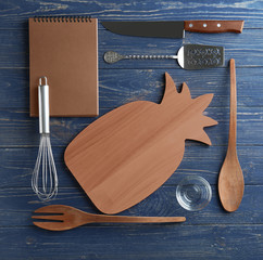 Kitchen utensils on wooden background