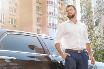 Handsome young man in white shirt standing near car outdoors