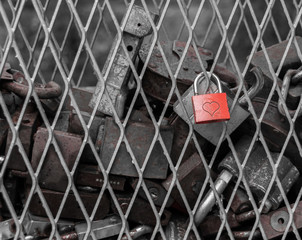 A red heart shaped lock connected to the cage with old rusty locks