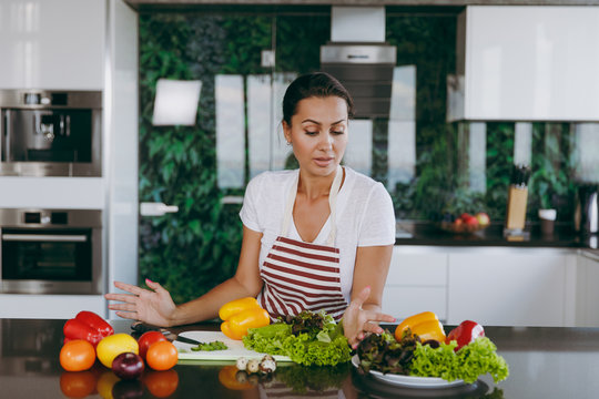 A young confused and thoughtful woman in apron decides what to cook in the kitchen. Healthy food - Vegetable salad. Diet. Dieting concept. Healthy lifestyle. Cooking at home. Prepare food