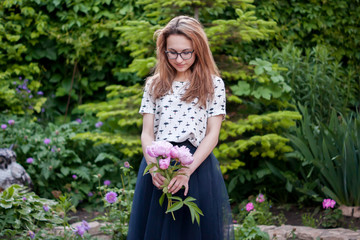 Girl with peonies on nature