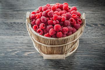 Raspberries in bucket on wooden board
