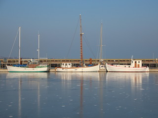 Three Boats in Frozen Cold Harbor Water at Wintertime