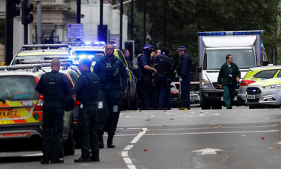 Police officers stand in the road near the Natural History Museum, after a car mounted the pavement injuring a number of pedestrians, in London