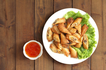 Veg. Spring Rolls on white dish on wooden table.Thai food and selective focus.