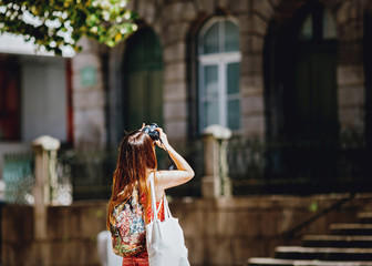 Young girl traveler photographing
