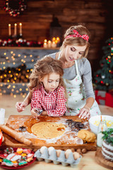 Merry Christmas and Happy Holidays. Family preparation holiday food. Mother and daughter cooking cookies in New Year interior with Christmas tree.