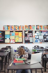 Tired schoolboy sleeping on stack of book sitting in classroom