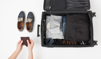 Male hand put things in suitcase on white